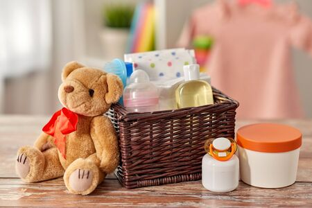 baby things in basket and teddy bear toy on table Stock fotó