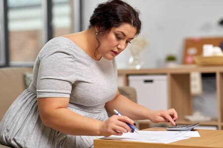 woman with papers and calculator working at home Stock Photo