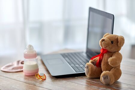 baby milk formula, laptop, soother and teddy bear