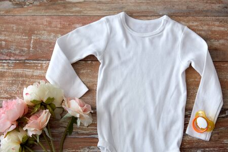 baby clothes, babyhood and clothing concept - white bodysuit with soother and flowers on wooden table