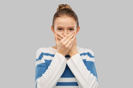teenage girl covering mouth by hands