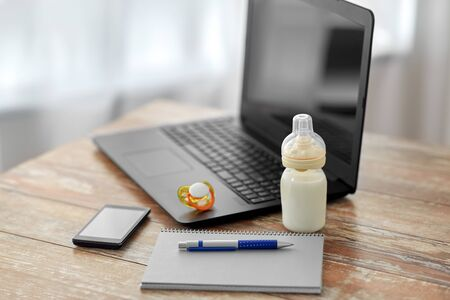 baby milk formula, laptop and notebook on table