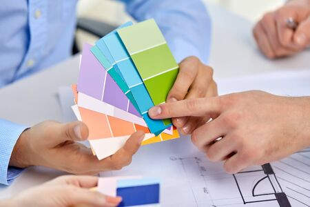 interior design, architecture and people concept - close up of designers team working with blueprint and color palettes