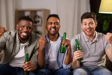 happy male friends or fans drinking beer at home