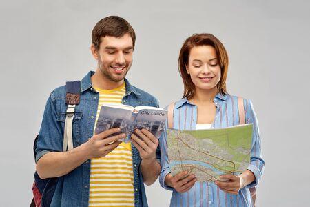 heureux couple de touristes avec guide de la ville et carte
