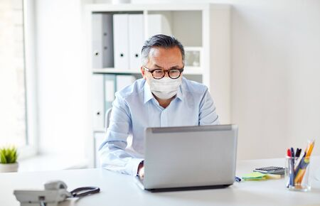 businessman in medical mask with laptop at office Stock Photo