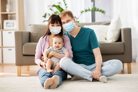 family with baby in medical masks at home