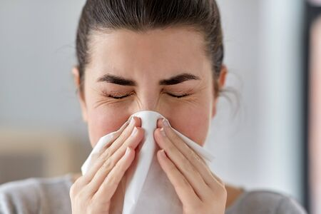 sick woman blowing nose in paper tissue at home