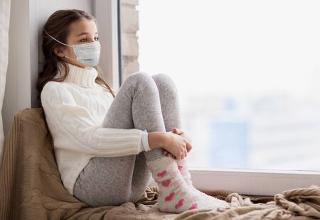 sad girl in medical mask sitting on sill at home