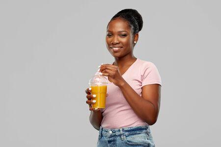 happy african american woman drinking orange juice