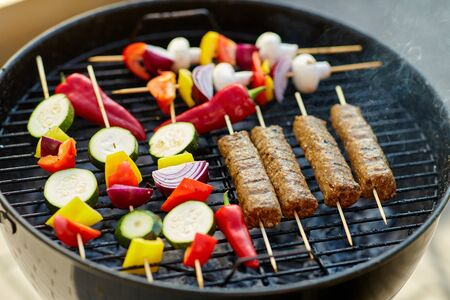 barbecue meat and vegetables roasting on grill