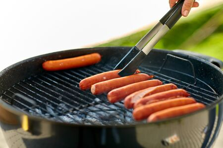 meat sausages roasting on hot brazier grill