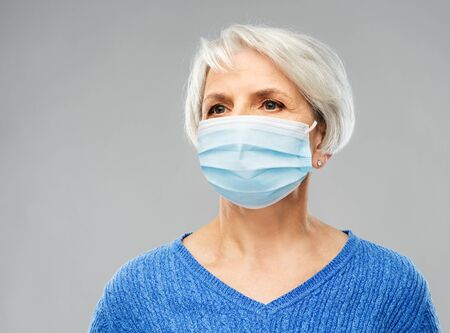 health, quarantine and pandemic concept - portrait of senior woman wearing protective medical mask for protection from virus over grey background