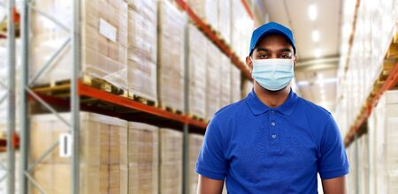 indian delivery man in medical mask at warehouse Foto de archivo