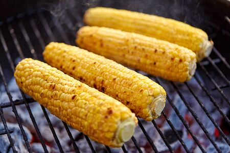 cooking, barbecue and food concept - close up of corn roasting on brazier grill outdoors Archivio Fotografico