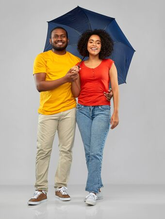 smiling african american couple with umbrella