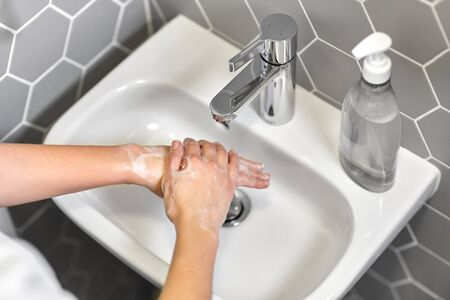 close up of woman washing hands with liquid soap Stock Photo