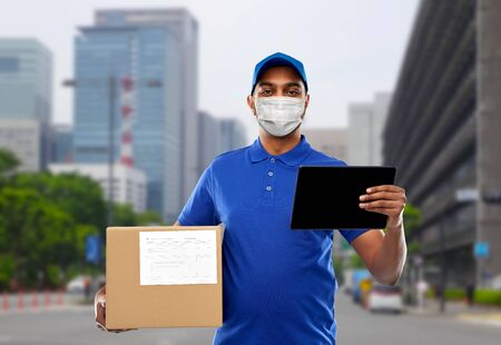 delivery man in mask with tablet pc and parcel box