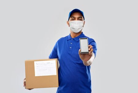delivery man in mask with cellphone and parcel box Stock Photo