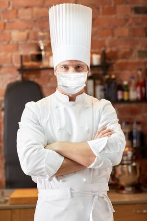 male chef in face mask at restaurant kitchen