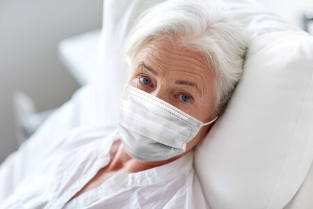 old woman patient in mask lying in bed at hospital
