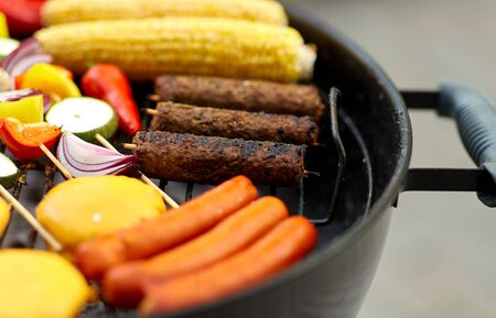 cooking, barbecue and food concept - close up of shish kebab meat, vegetables on bamboo skewers, burger buns with corn and sausages roasting on brazier grill outdoors
