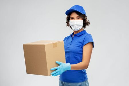 femme de livraison au masque facial tenant la boîte à colis