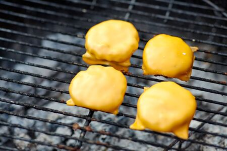 Close up of meat cutlet with cheese on grill