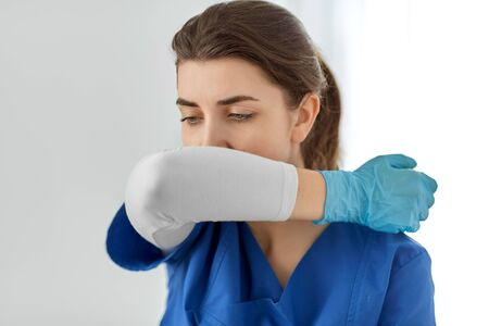 doctor or nurse coughing covering mouth with elbow