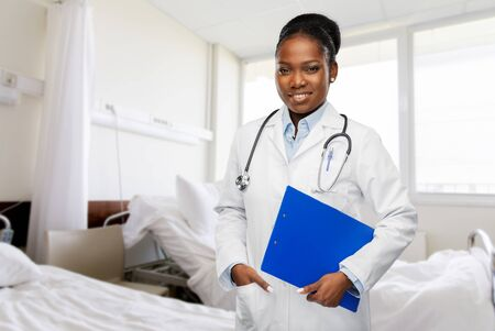 happy african doctor with clipboard at hospital
