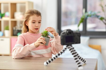 blogging, technology and people concept - happy smiling girl blogger with camera and home plant recording video Stockfoto