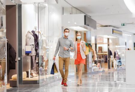 couple in medical masks with shopping bags in mall