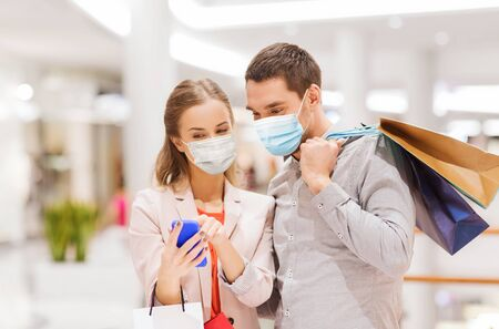 couple in masks with smartphone in shopping mall