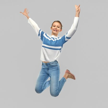 smiling teenage girl in pullover jumping