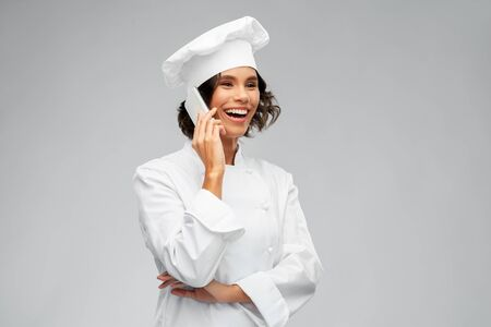 smiling female chef in toque calling on smartphone