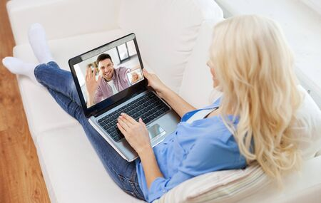 woman with laptop having video call with man