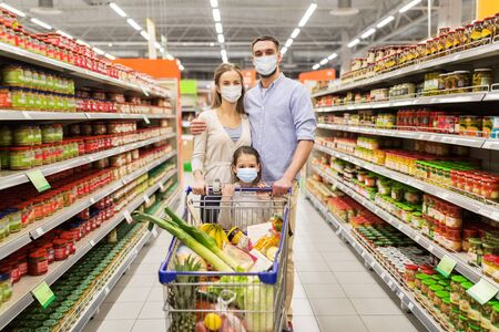 family with shopping cart in masks at supermarket
