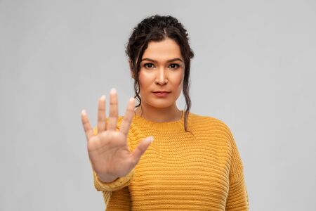 woman showing stop gesture over grey background