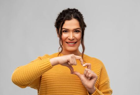 smiling young woman making hand heart gesture Standard-Bild