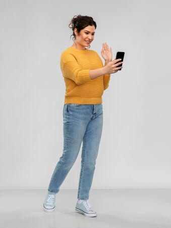 happy young woman having video call on smartphone Standard-Bild