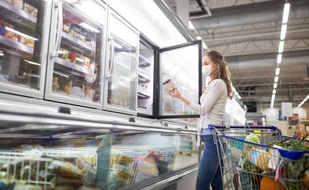 woman in mask choosing ice cream at grocery store