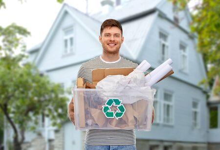 uśmiechnięty młody człowiek sortujący odpady papierowe nad domem