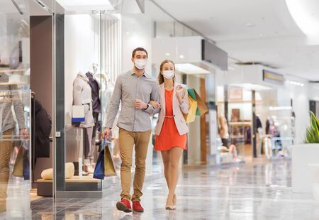 couple in medical masks with shopping bags in mall Stock Photo
