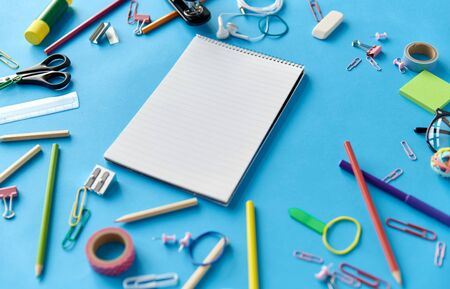 notebook and school supplies on blue background