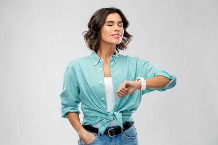 people concept - portrait of happy smiling young woman in turquoise shirt with smart watch breathing over grey background