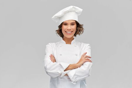 cooking, culinary and people concept - happy smiling female chef in toque with crossed arms over grey background Standard-Bild