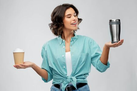 people concept - portrait of happy smiling young woman in turquoise shirt comparing thermo cup or tumbler with disposable paper coffee cup over grey background
