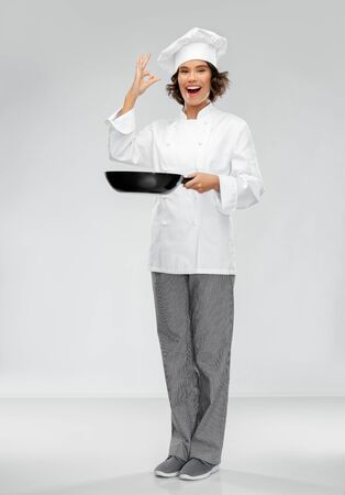 cooking, culinary and people concept - happy smiling female chef in toque with frying pan showing ok hand sign over grey background