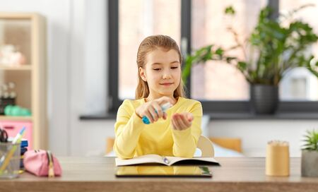 little student girl with hand sanitizer at home