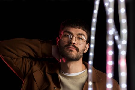 man in glasses over neon lights at nightclub Stock Photo